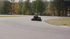 Two drivers on a go-kart track pass by the camera. Go-kart race. Go-kart race. Two drivers on a go-kart track pass by the camera stock video