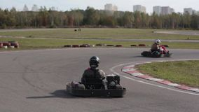 Two drivers in karts are moving very slowly on a ride. Go kart track. Go kart track. Two drivers in karts are moving very slowly on a ride stock video