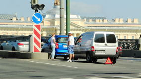 Two drivers talking near accident vehicles. Two drivers talking near the site of the accident vehicles on a busy street, St Petersburg, Russia stock footage