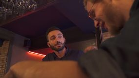 Two drunk friends sit at the bar. Two friends are relaxing in the club in the evening. Red-haired guy in glasses with a beard takes a cocktail. Leisure and stock video