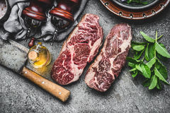 Two Dry aged raw beef steaks with meat cleaver and condiment on dark rustic concrete background. Top view royalty free stock images