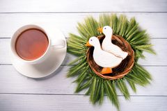 Two duck shaped ginger cookies with basket nest  wreath with spikelets top view with tea cup on a white wooden background. Royalty Free Stock Photography