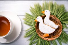 Two duck shaped ginger cookies with basket nest  wreath with spikelets top view with tea cup on a white wooden background. Stock Photography