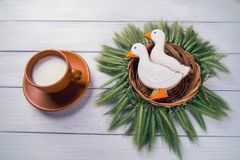 Two duck shaped ginger cookies with basket nest  wreath with spikelets top view with tea cup on a white wooden background. Royalty Free Stock Image