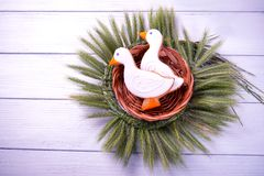 Two duck shaped ginger cookies with basket nest  wreath with spikelets top view on a white wooden background. Toned. Royalty Free Stock Photos