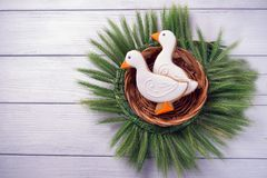 Two duck shaped ginger cookies with basket nest  wreath with spikelets top view on a white wooden background. Toned. Stock Images