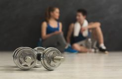 Free Two Dumbbells And Blurred Couple At Gym Stock Photography - 132614222