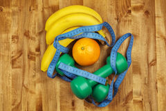 Two dumbbells, a centimeter, bananas and an orange lie on a wood Royalty Free Stock Photo