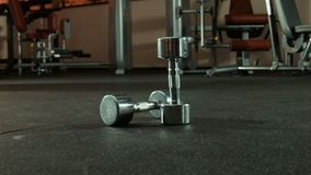Two dumbbells in gym. Wide shot stock footage