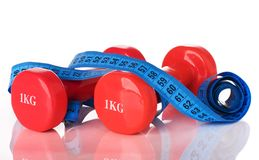Two dumbbells and measuring tape Royalty Free Stock Photography