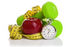 Two dumbbells, red apple, measuring tape. Royalty Free Stock Image