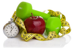 Two dumbbells, red apple, measuring tape. Royalty Free Stock Photos