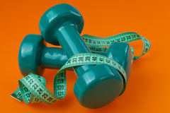 Two dumbells with measuring tape Royalty Free Stock Images