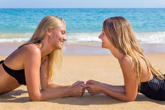 Two dutch girls lying opposite on beach. Two young caucasian women lying opposite on beach Royalty Free Stock Photography