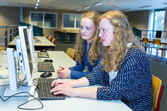 Two dutch students working on computer in school. Two caucasian girls working at computer in study room of high school Stock Photography