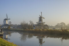 Two dutch windmills in the fog Stock Images
