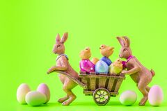 Free Two Easter Bunnies And A Cart With Lots Of Colorful Easter Eggs And Chicks Stock Image - 213073831