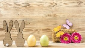 Two easter bunnies and two easter eggs. With flowers and butterflies Stock Photography