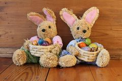 Two easter bunnies with eggs. Two easter bunnies sitting in front of a wooden box with eggs Royalty Free Stock Photography