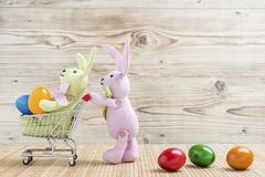 Two easter bunnies with shopping cart and colorful eggs. In front of a wood background Royalty Free Stock Images
