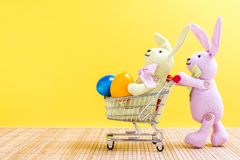 Two easter bunnies with shopping cart and easter eggs Stock Photo