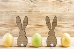 Two easter bunnies with three easter eggs. In front of a wood background royalty free stock photography