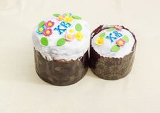 Two Easter cakes different sizes on the tablecloth. Two Easter cakes different sizes decorated with white icing and colorful sugar decors, wrapped in special Royalty Free Stock Photography