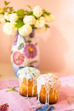 Two easter cakes. On pink towel and hydrangea bouquet in vase on background Stock Photos