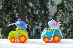 Easter cars with a eggs. Two Easter cars tied up with colored ribbons go on the table on the background of greenery stock image