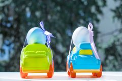 Two Easter cars. Tied up with colored ribbons go on the table on the background of greenery royalty free stock photography