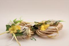Easter decoration. Two nests on soft background. Two Easter decorative nests with yellow flowers and green leaves Stock Images