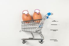 Two Easter egg is riding in the shopping trolley stock image