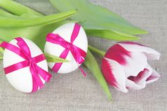 Two Easter Eggs with Bows and Tulip on Bagging Royalty Free Stock Images