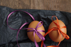 Two Easter eggs with bright color tapes on black crumpled paper Royalty Free Stock Images