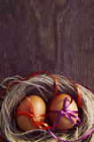 Two Easter eggs with bright tapes in a nest Royalty Free Stock Images