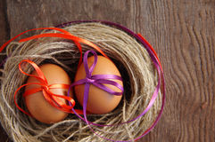 Two Easter eggs with bright tapes in a nest Stock Photo