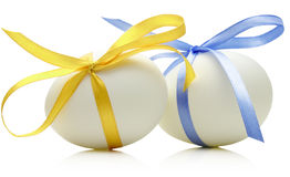 Two Easter eggs with festive blue and yellow bow  on whi Stock Photography
