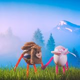 Two Easter eggs hikers in a hats with backpacks. Standing in a spring grass and enjoy the foggy mountain valley in a light of sunrise Royalty Free Stock Images