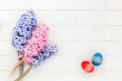 Two Easter eggs and hyacinths on white tablecloth. Top view Stock Photos