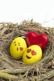 Two Easter eggs painted with emojis, one in love and other kissing, placed into a nest in isolated white background stock photos