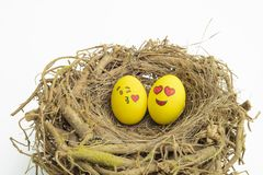 Two Easter eggs painted with emojis, one in love and other kissing, placed into a nest in isolated white background royalty free stock photo