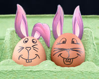 Two Easter eggs with painted faces and bunny ears. Two Easter eggs with painted faces and violet bunny ears Royalty Free Stock Photo