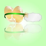 Two Easter golden eggs tied a green ribbon with a tag on a light green background. Stock Photo