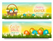 Two Easter Sale banners. Colorful eggs in green grass. Vector Stock Photos