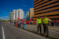 Two ecuadorian policemen supervising protesters Royalty Free Stock Images