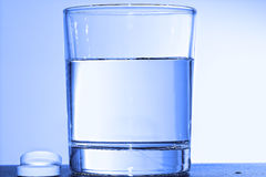 Two effervescent tablets and glass with water Royalty Free Stock Images