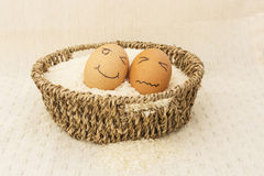Two egg in a brown Basket on rice. And happy,sad egg stock photos