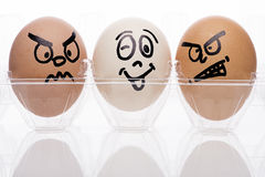 Two egg characters. Displaying angry emotions towards a single white egg Stock Photo