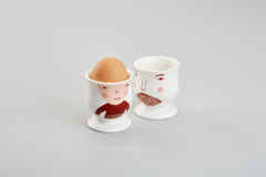 Two egg cups and a brown egg  in grey background Royalty Free Stock Photos