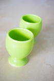 Two eggcups. Two green eggcups on wooden background Royalty Free Stock Photography